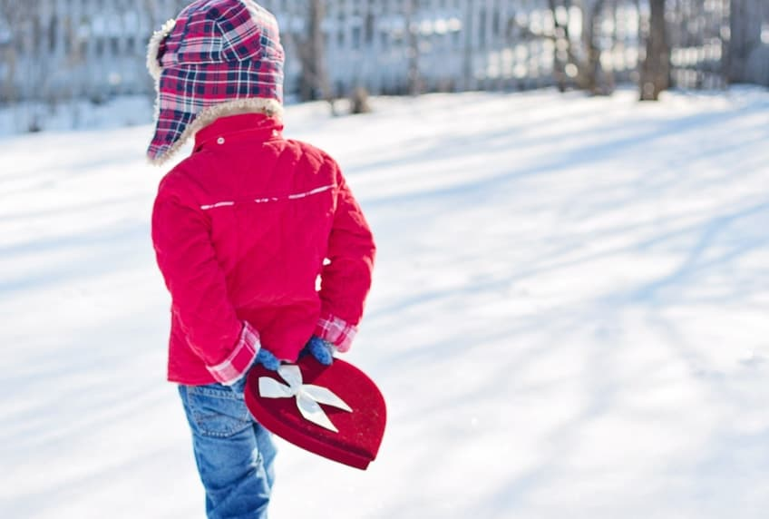 Little boy carrying heart shaped gift